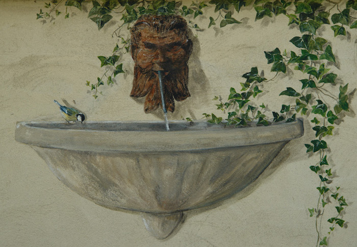 trompe-l'oeil mural painted on an exterior wall with a font and a Bacchus head. acrylic