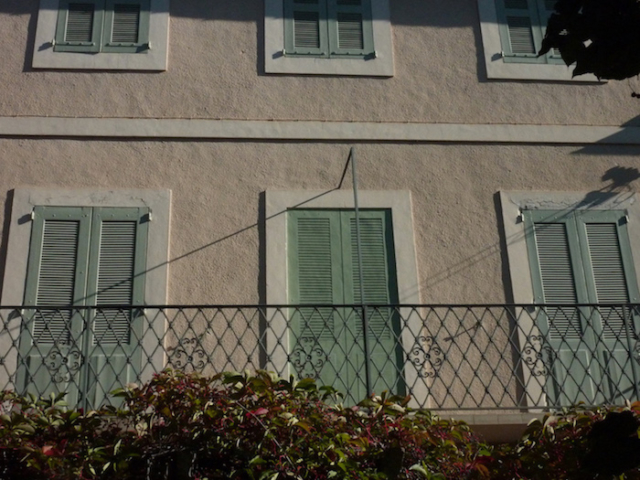 trompe-l'oeil mural painted on an exterior wall with the same design of the real  green shutters. It is the middle one who is painted. acrylic technic