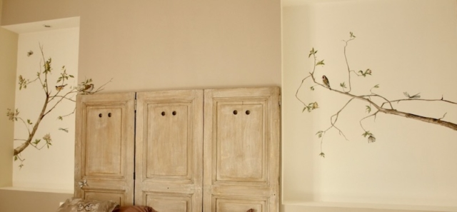 Décor painted on the walls of a bedroom with birds and branches of apple tree in blossom. acrylic technic