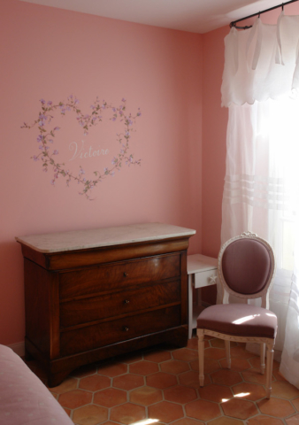 Décor painted on the pink wall of the Victoire's bedroom with a big heart. The heart is painted as garland of sweet peas (pink) and inside the name of the little girl