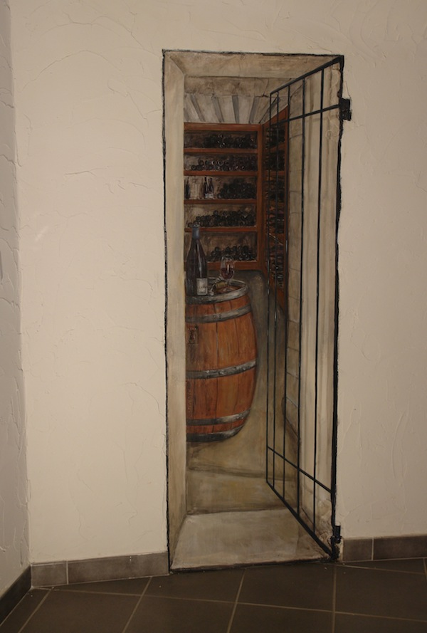 Illusion of a wine cellar painted on a wood door in the back of the restaurant room. acrylic technic
