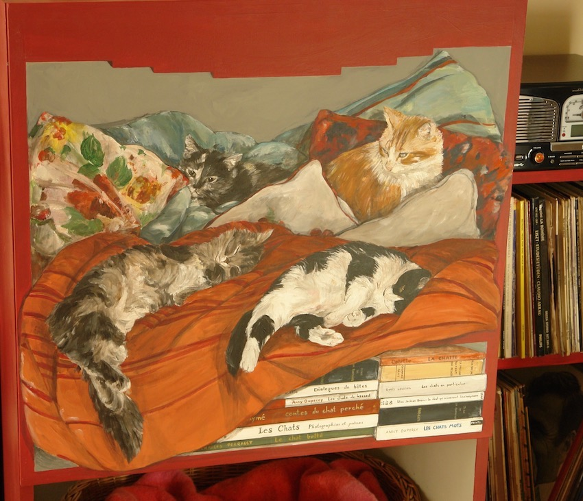 Trompe-l'oeil of books about cats and 4 cats painted on a wood cupboard. The cats are on sweet cushions with warm colors. acrylic on wood