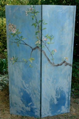 a branch of apple tree in blossom on  blue sky painted on the recto side of the screen. mixed media on wood