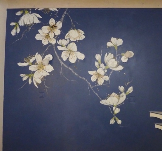 Big white flowers of cherry tree painted on the deep blue wall of the bedroom en suite. acrylic technic