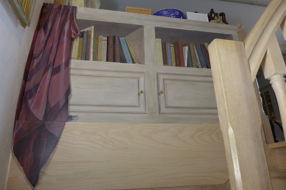 Fake books in a cupboard and purple curtain on the left side with little mouse, painted on wood panel fixed on the back of the real library. mixed media on wood