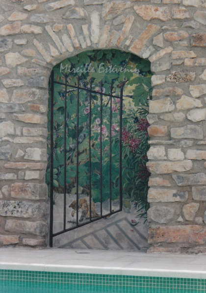 Trompe-l'oeil mural painted on an exterior wall, with a cat playing behind the gate opened on the garden. This décor is painted near the swimming pool. acrylic technic