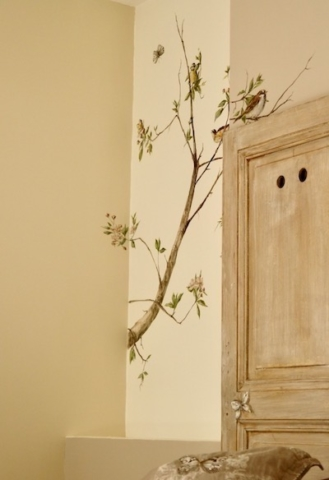 Birds and branches of apple tree in blossom painted on the walls of a bedroom. acrylic paint