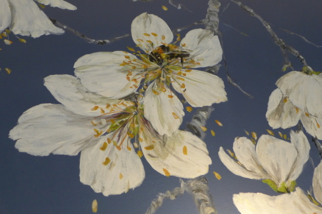 Detail of the big white flowers of cherry tree with a bee, painted on a blu wall in the bedroom en suite. acrylic technic