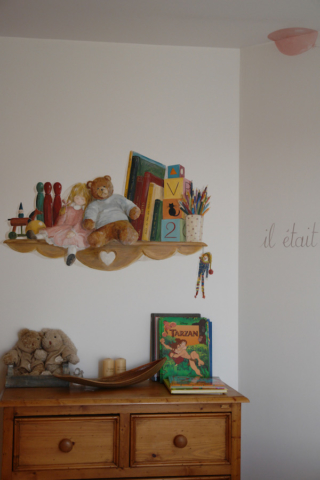 Toys and books on shelves painted on the wall of the twins bedroom with acrylic technic
