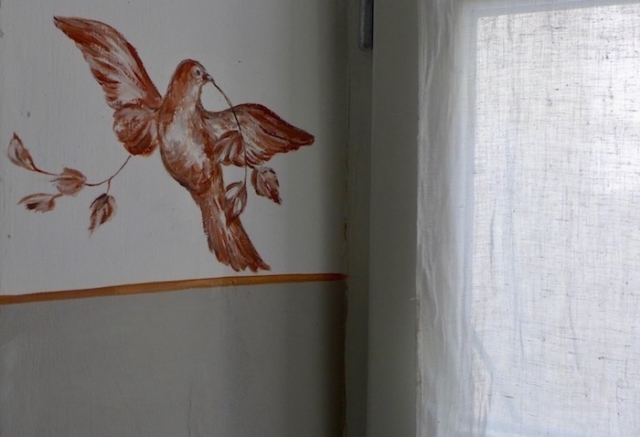 Bird painted on the wall of the red bathroom, inspired by the theme of the curtains. acrylic