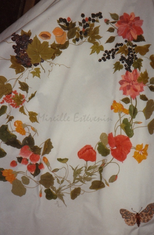 Wreath of flowers and fruit painted on cotton table cloth. Warm colors. Order by the shop in Paris, Le Bain Marie. Cloth paintings